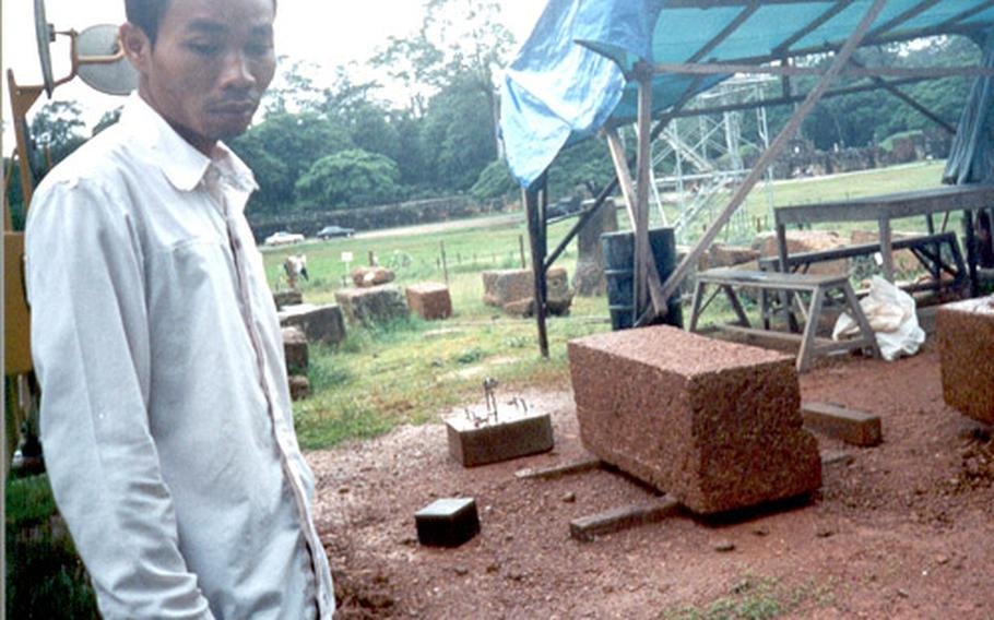 Tuan, 20, stands near temple group undergoing restoration compliments of Japanese donations.