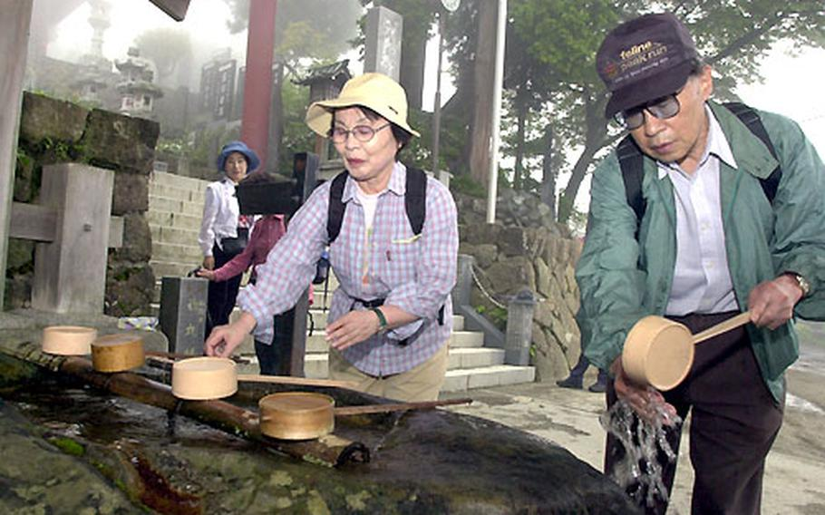 Japanese wash their hands in an act of purification before entering the shrine on Mount Mitake.