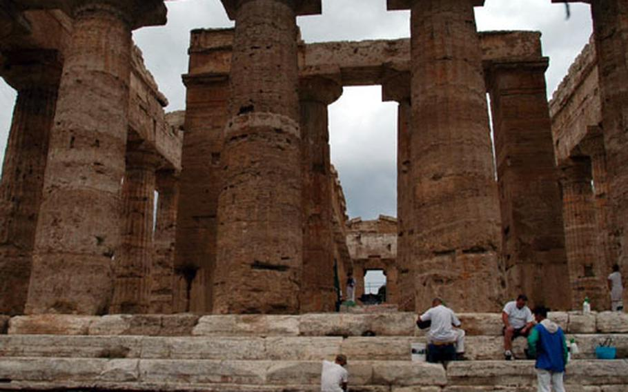 Columns of the Temple of Neptune seem to dwarf archaeologists as they work on the temple's base.