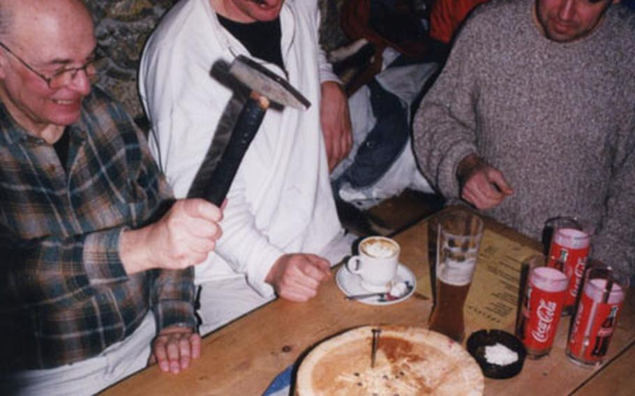 A popular hut game involves pounding nails into a log. The loser must buy a round of schnapps for the other players.