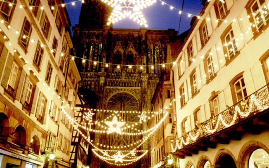 Fairy-light stars adorn the Rue Mercière, which leads toward the illuminated west facade of the Gothic cathedral at the Christmas market in Strasbourg, France.