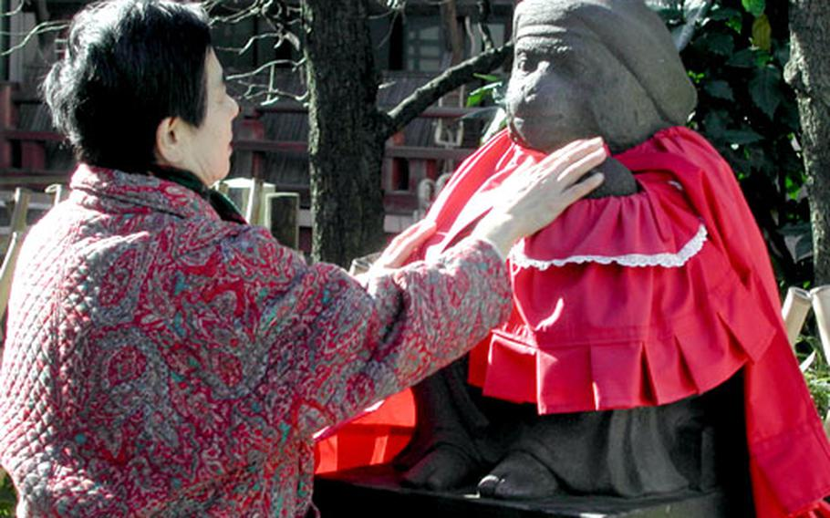 A lady touches a statue of a baby monkey held in a mother monkey's arms at Hie Shrine.