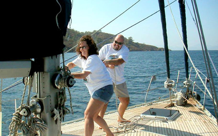 Angela Guthrie and Bruce Rehberg hoist the main sail of the Anna Maria as it sets from the port of Fethiye, Turkey.