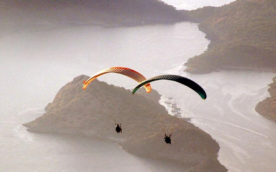 Paragliding over the Ölüdeniz area in southern Turkey are group member Bruce Rehberg, left, and the Anna Maria's first mate, Jill Lumenta.