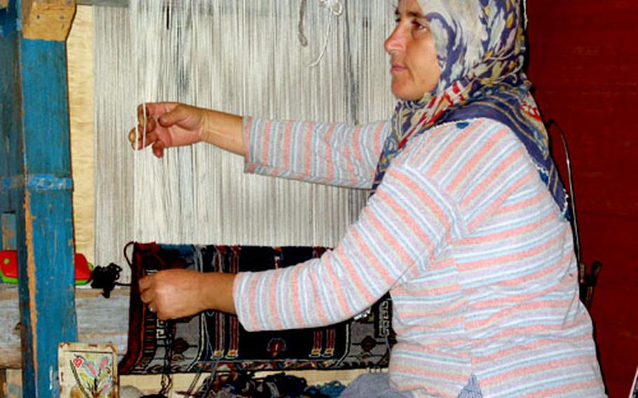 A member of the Kül family shows the sailing group how to weave a Turkish carpet while they visit her home above Kapi Creek, near the town of Göcek, Turkey.
