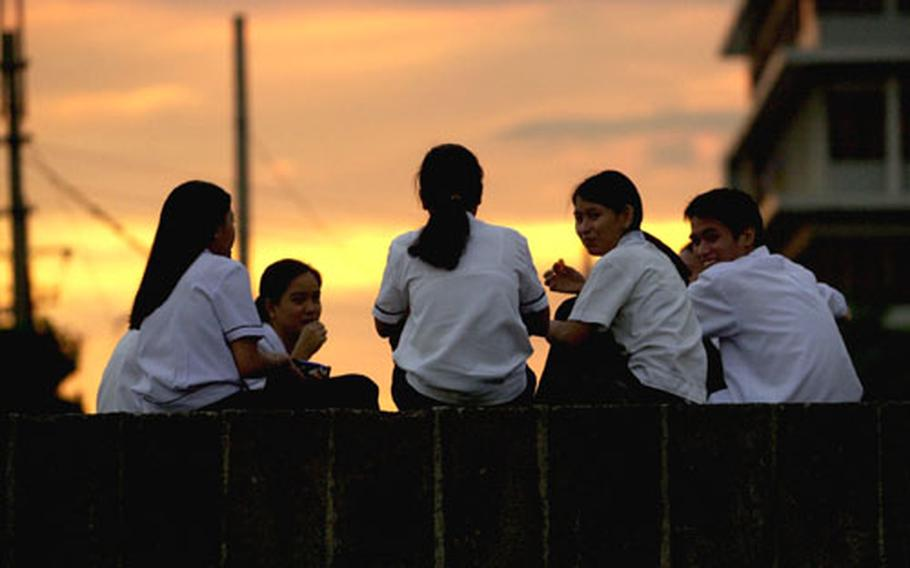 Philippine high school students enjoy some snacks and chat as the sun sets on the walled city of Intramuros in Manila. Below: A majestic view of one of St. Augustine Church's chandeliers and the arched ceiling in its main sanctuary.