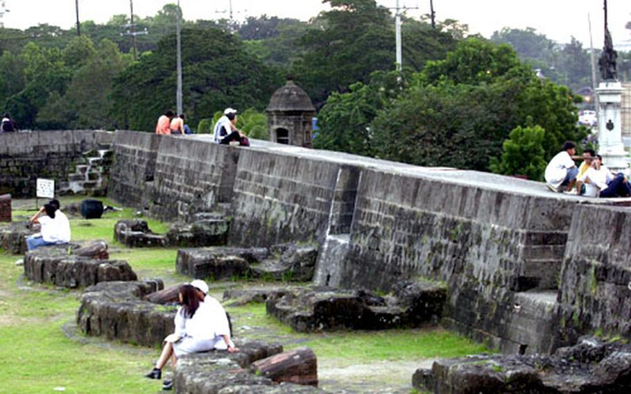 Along the walls of Intramuros in old Manila, couples relax and enjoy the warm evening.