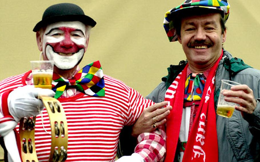 Colorful clown characters hoist a brew at Fasching celebrations in Cologne, Germany.