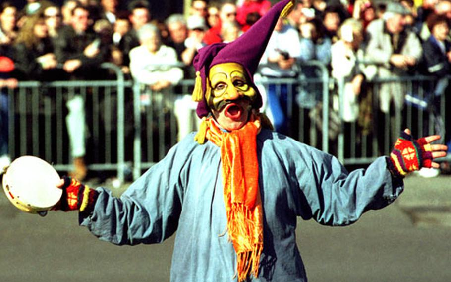 """A jester clowns around during the """"Bataille de Fleurs"""" (battle of the flowers) parade during Carnival in Nice, France."""