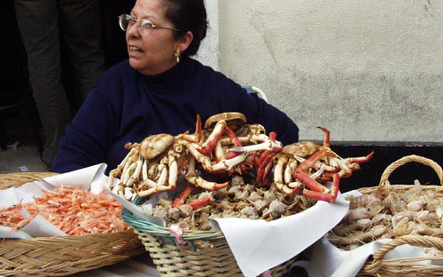 A woman sells a table full of local seafood on a city street in Cádiz, Spain, during last year's Carnival.