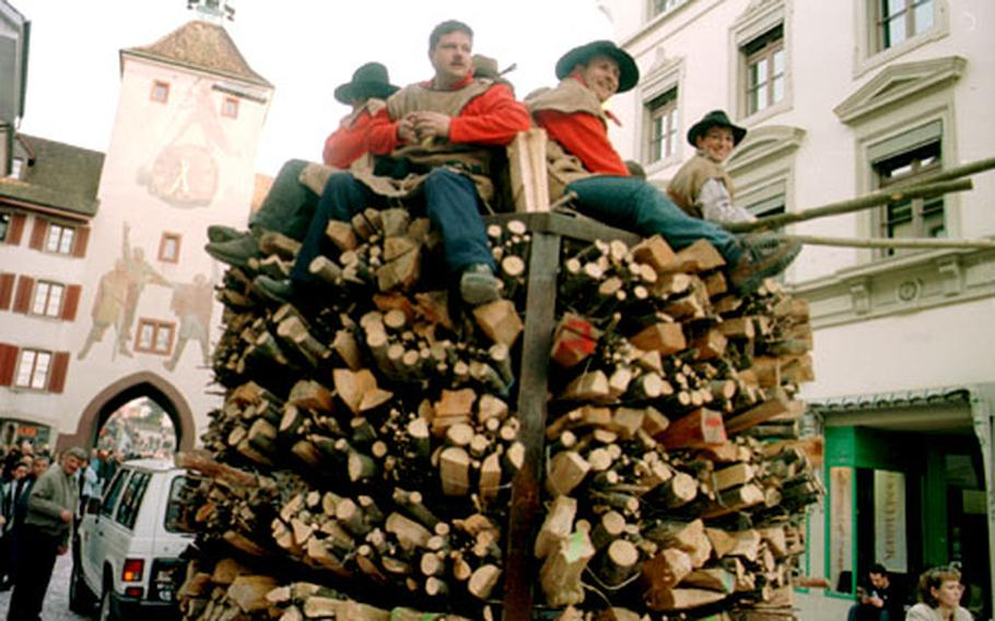 Members of a Fasnacht club ride their creation to the start of the fire parade. Later they will return through the medieval upper-town gate of Liestal, behind them, with their load on fire.