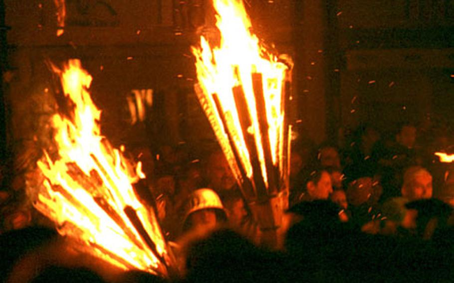 """Dry pine sticks are wrapped around a fresh birch branch to make what the Swiss call the """"Chienbäse,"""" or """"pine broom."""" Here, excitement erupts along with the fire as the brooms are set ablaze. Fasnacht club members, wearing hats and protective gear, then carry the burning brooms through the masses of spectators."""
