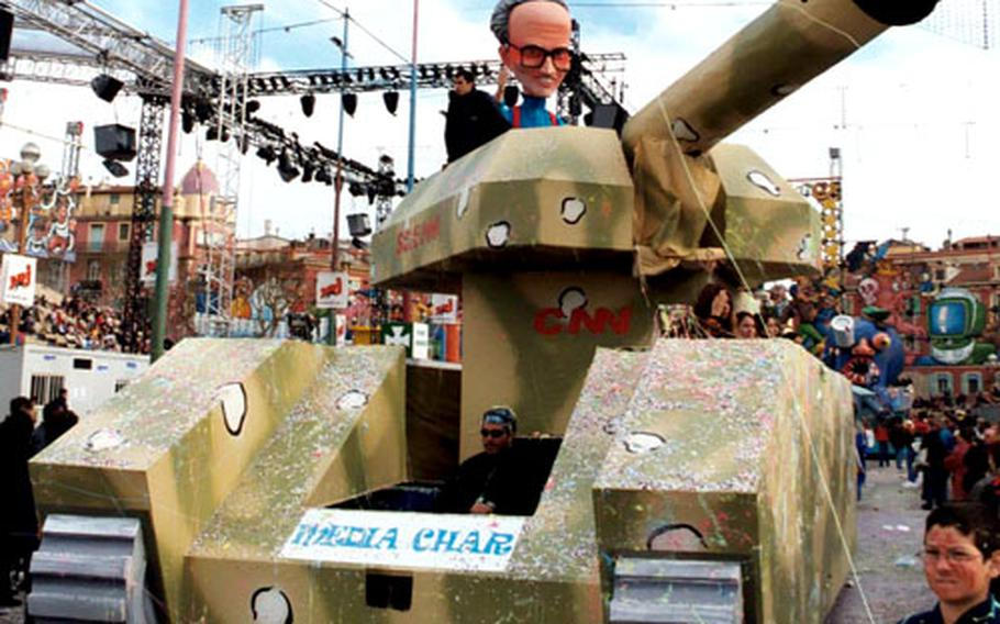 A tank driven by a papier-mâché Larry King blasts war news in the form of confetti out of its main gun during the parade at the 2003 Nice Carnival.