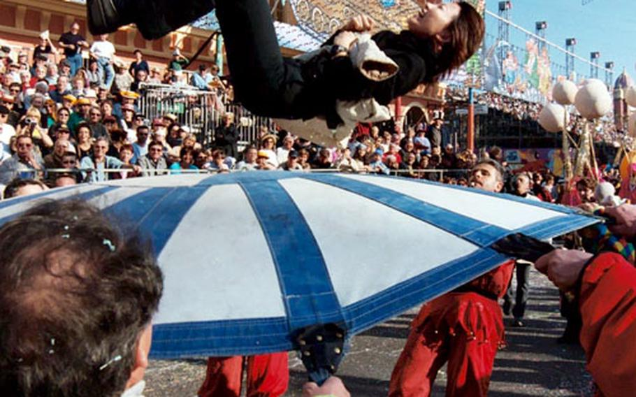 Clowns pick up a bystander and toss her on a tarp during last year's Nice festivities.