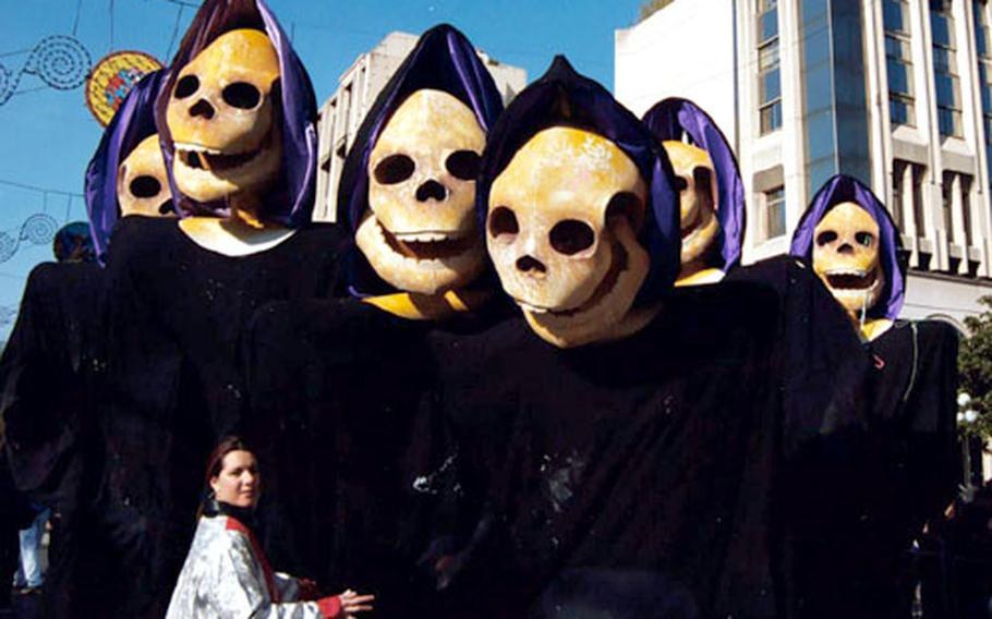 A group of Grim Reapers, 12 feet tall, pause with a carnivalgoer at Nice in 2003. The group represents the 11 o'clock Grim Reaper News teams -- the worse the news, the better for the news team.