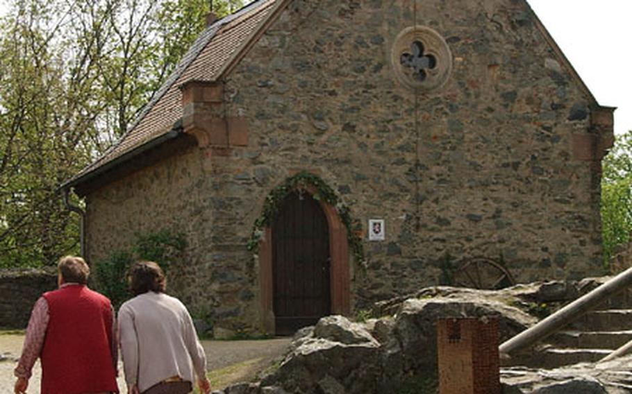 Two women walk up the hill to the chapel at Burg Frankenstein. The chapel, restored in the 1800s, is used today for weddings and other services.