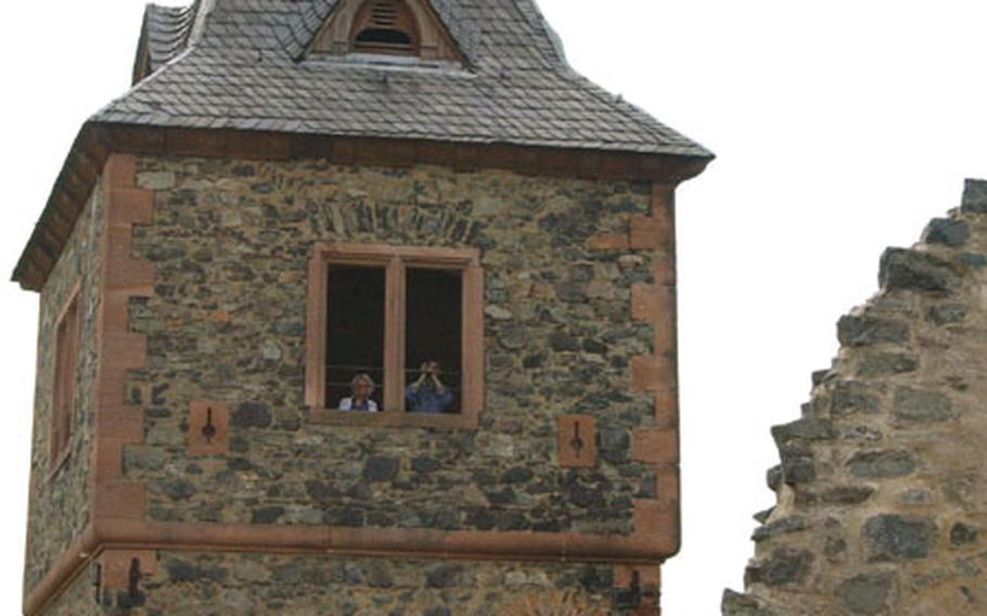 A couple peers out the tower at Burg Frankenstein. The tower offers a great view all the way to the Rhine River.