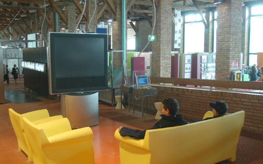 """Visitors to the Citta' della Scienza sit in front of a big-screen TV to watch a short presentation on communications in the center's """"Signs, Symbols, Signals: Communicating Today"""" section."""