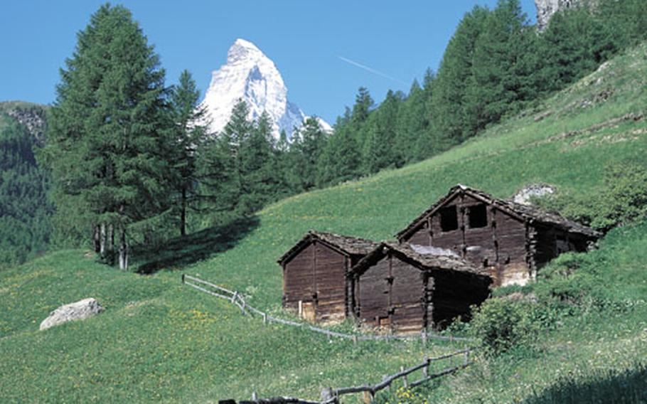 The tip of the 14,692-foot Matterhorn, still covered with snow in the summer, rises above the mountain slopes surrounding the resort of Zermatt in the canton of Valais.