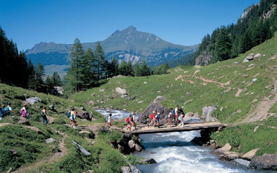 Hikers cross a bridge spanning the Geltenbach River near the mountain village of Lauenen in the highlands south of the Swiss capital of Bern.