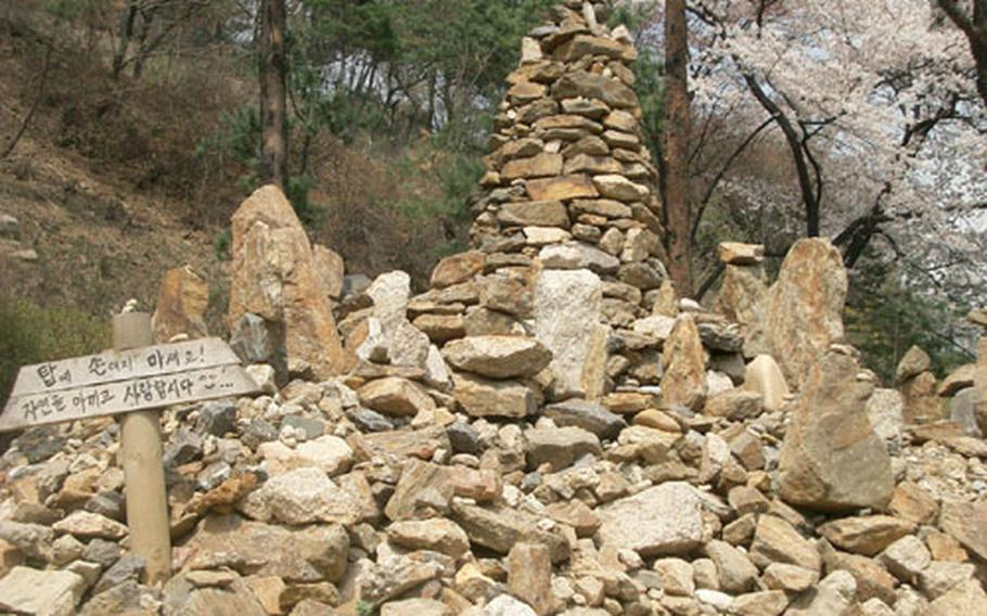 """A rock tower along one of the paths in the lower part of Namsan park. The sign reads, """"Don't touch a tower! Let's cherish and love nature!"""""""