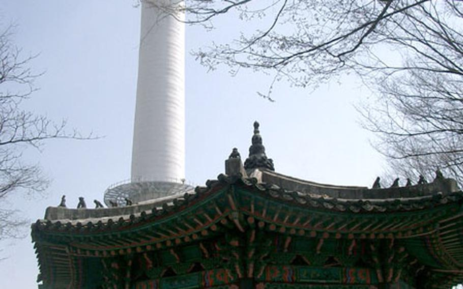 The old and the new ... Seoul Tower rises above a historic pavilion crowned with watching monkeys.