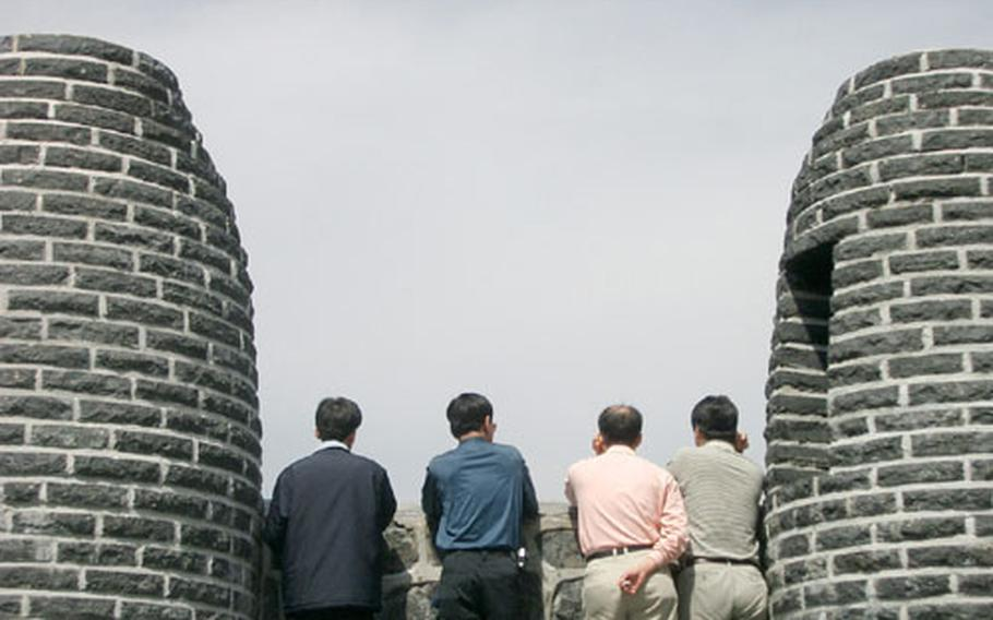 A group of men pause and check out the view from a series of huge brick ovens once used as signal fires to relay emergencies or border attacks from the outlands back to the capital, Seoul.