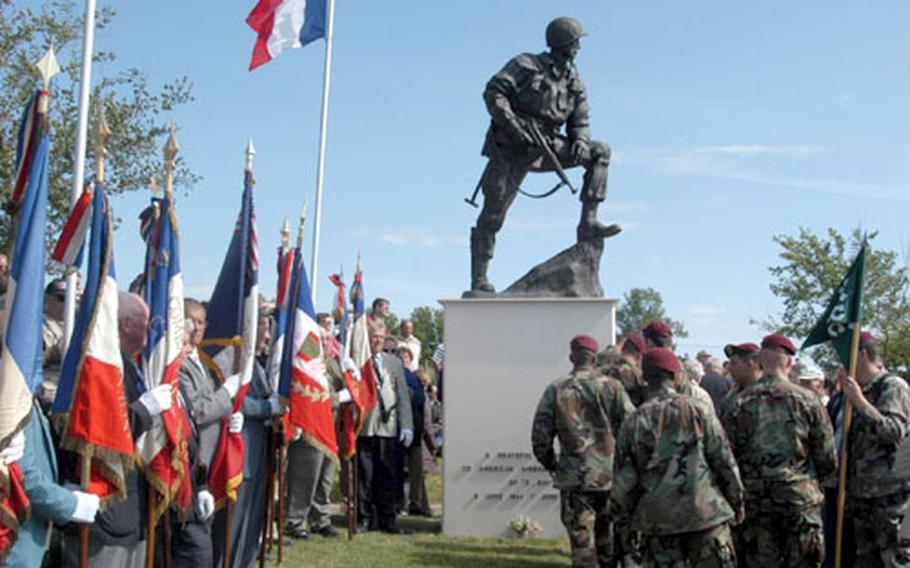 French veterans and American paratroops gather at the statue of a U.S. paratrooper at La Fière, near St.-Mére-Eglise.