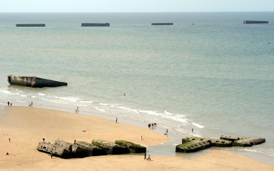 Beachcombers are dwarfed by the huge concrete leftovers of Port Winston, the artificial harbor at Arromanches. These big camions were dragged by tow ships across the English Channel and dropped into position to form an artificial harbor, allowing the British to bring in large amounts of supplies safely.