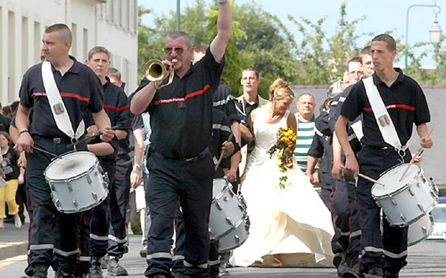 Firefighters escort a colleague and his bride through the streets of Bayeux.