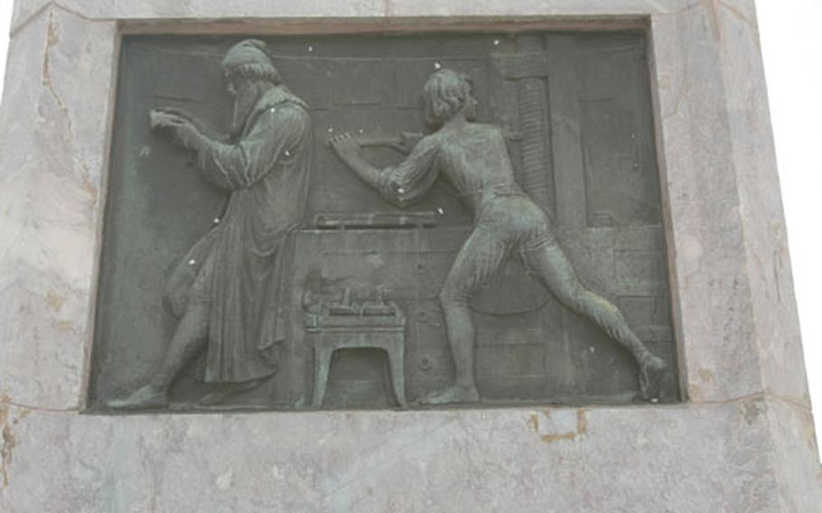 Detail work on the pedestal of a statue of Johannes Gutenberg shows a worker using a printing press while Gutenberg looks over the results.