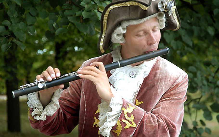 Dressed in period costume, a musician entertains visitors to Park Sanssouci.