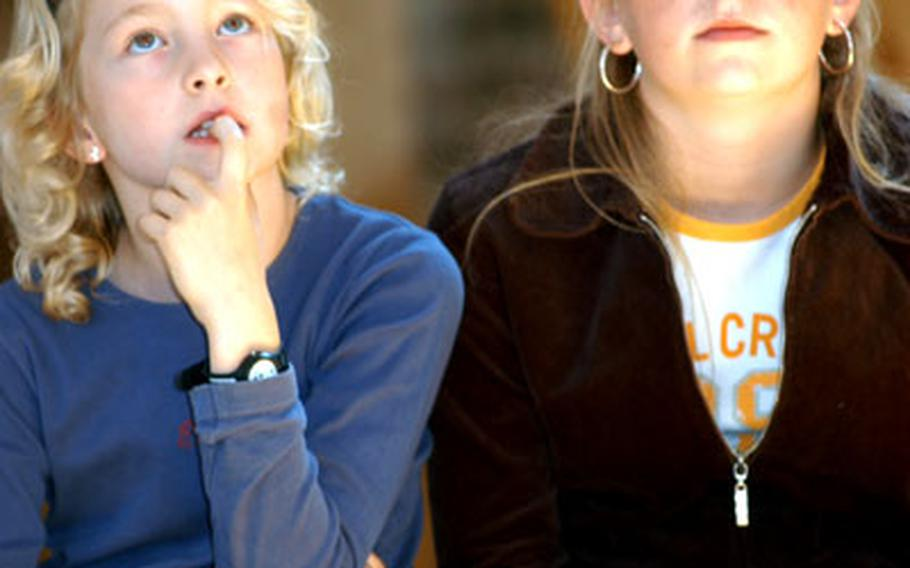 Nine-year-old Paula Jungheinrich, left, and her sister, Hannah, 12, both of Bad Homburg, watch a demonstration in the upstairs loft of the math museum.