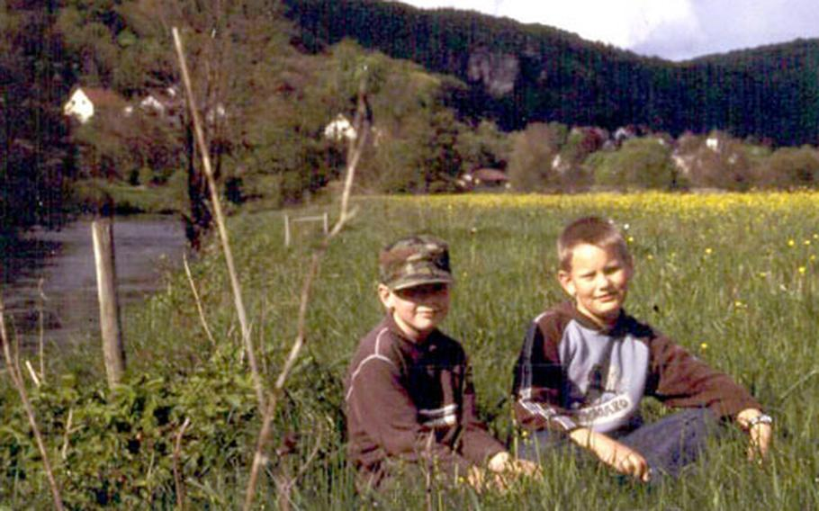 Florian, left, and Oliver pose for a photo in a meadow along the Wiesent River. Like many children, they like to watch anglers fish and are happy to help free the fish after they are caught.