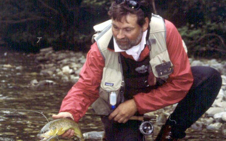 Rudi Heger prepares to return a brown trout caught in the Rote Traun to the river. Heger, owner of Traun River Products GmbH, is one of Europe's most famous fly-fishing personalities. He attended college in California and has fished many North American rivers.