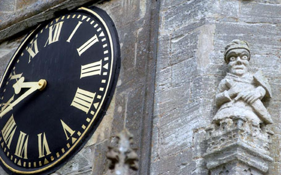The church clock is protected by a wide-eyed guardian carved in stone.