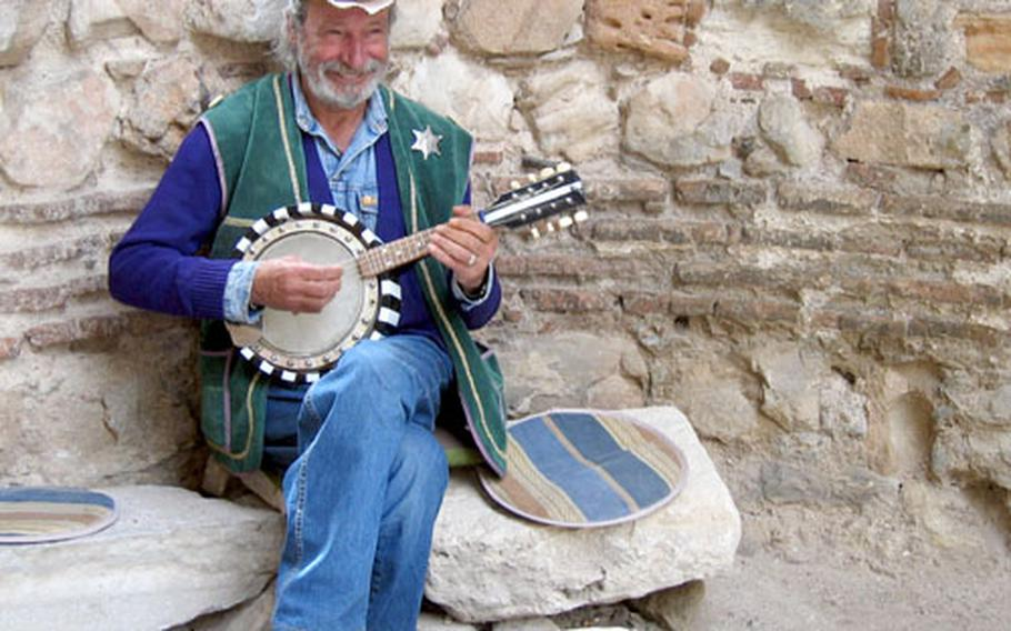 A musician dressed in his version of cowboy attire, complete with sheriff's badge, plays for donations amid some seaside ruins in Nesebur.