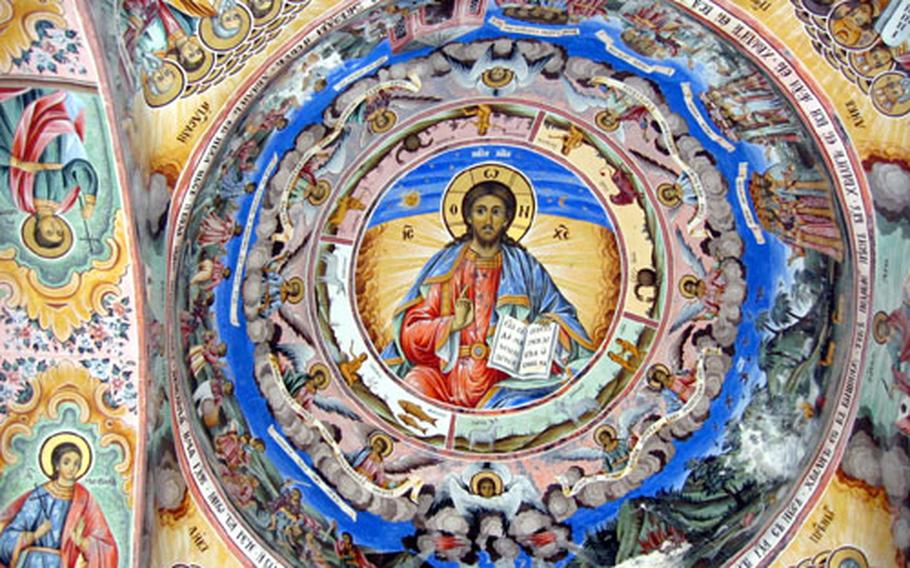 Vividly colored frescoes adorn the walls beneath the porticoes of the Church of the Nativity of the Virgin at Rila Monastery.