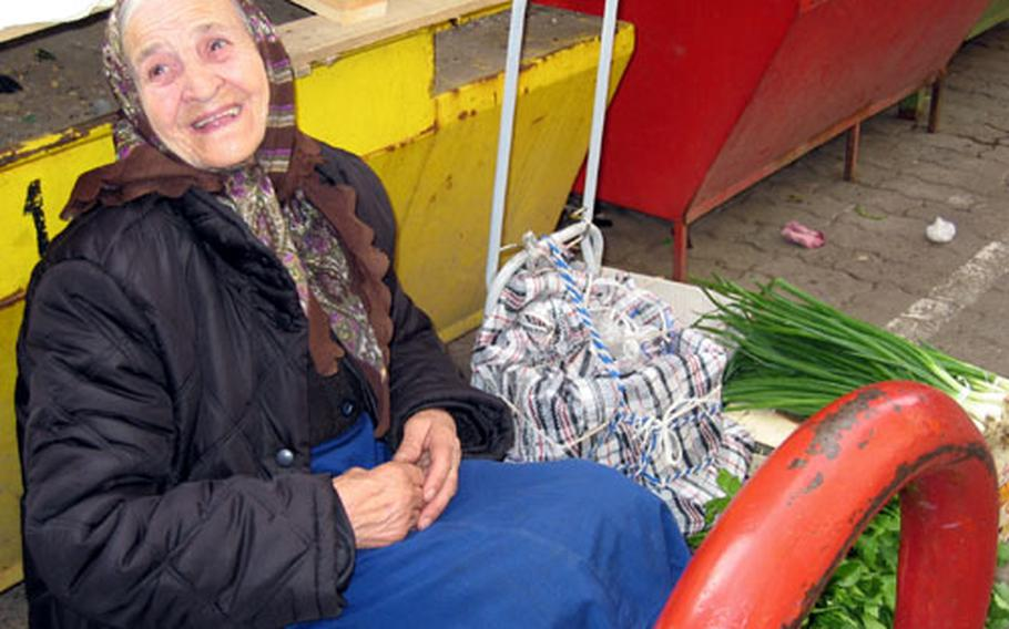 A vendor sits with her onions and other fresh produce at an outdoor market in Sofia. Fresh breads, cheeses, fish, clothing and handmade tools were all available at the market.