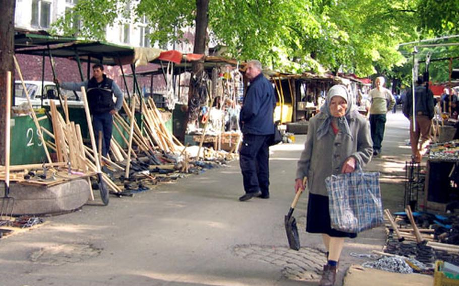 With a newly-purchased shovel in hand, a woman walks past stalls selling hand-made tools in Sofia, Bulgaria.