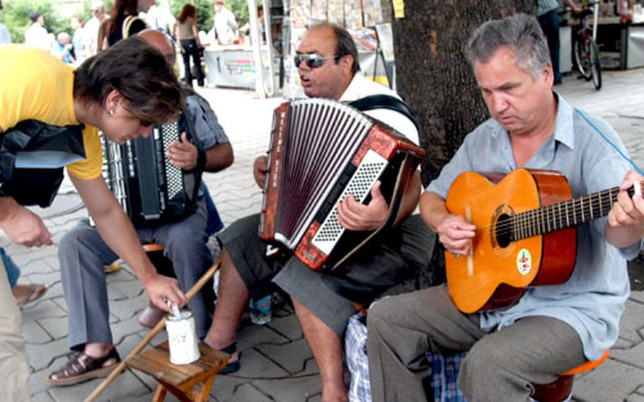 Streetside musicians perform in downtown Sofia near the bustling open-air market. Walking the streets of Sofia is a tour of the unpredictable. Stray animals are common, as are businessmen and politicians in pressed suits.