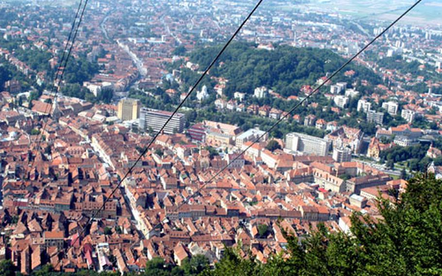 From a cable car, an impressive view of the tidy city of Brasov in the heart of Romania. Tourists often come here on their way to the Carpathian Mountains.