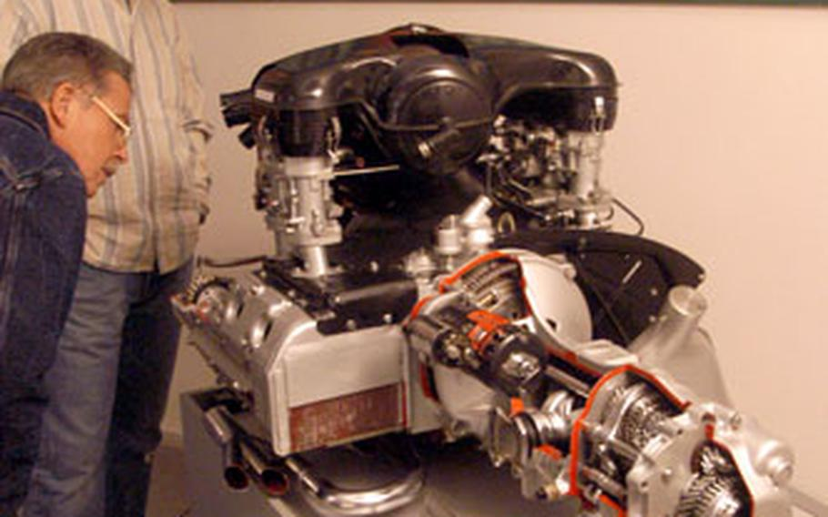 Visitors to the Porsche Museum examine a six-cylinder, air-cooled engine and transmission from a Porsche 911.