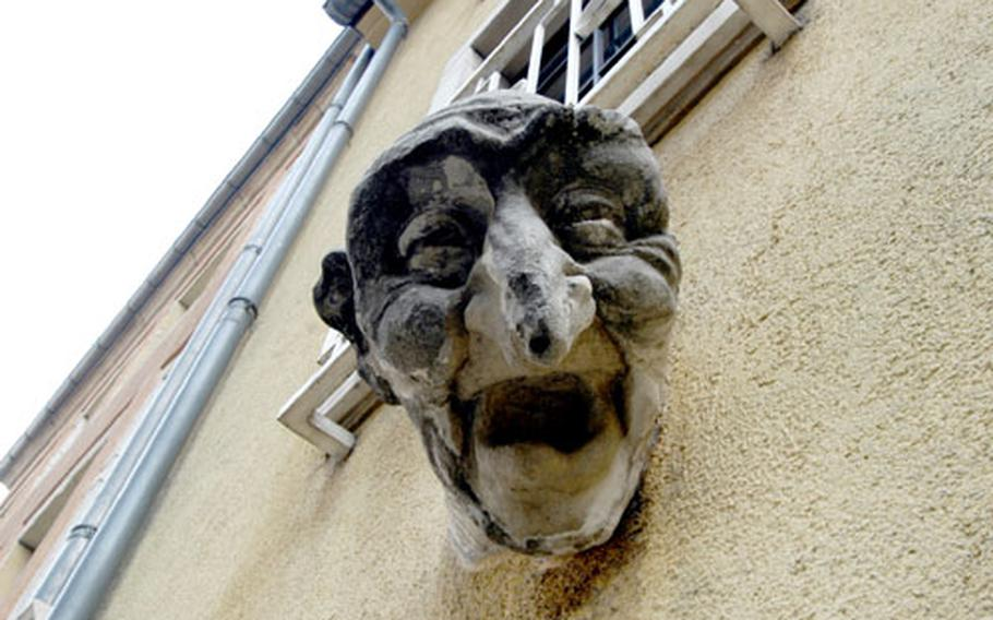 A strange head statue stands above a doorway in Luxembourg's old town.