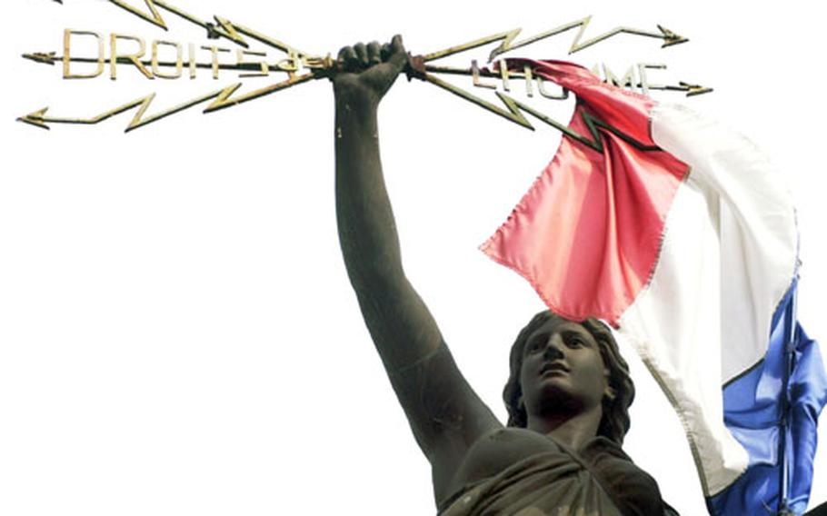 """A statue of Marianne, the symbol of France, holds aloft lightning bolts with the words """"Droits de l'homme,"""" or """"rights of man."""" The statue is in the little town Pézenas, near Bezier in the Languedoc region of southwestern France."""