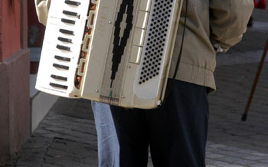 A musician carries his accordion down Ribeauvillé's Grand Rue, after playing for tourists' change. The town has a long history of street musicians after the Count of Ribeaupierre offered them protection — for a fee — in the Middle Ages.