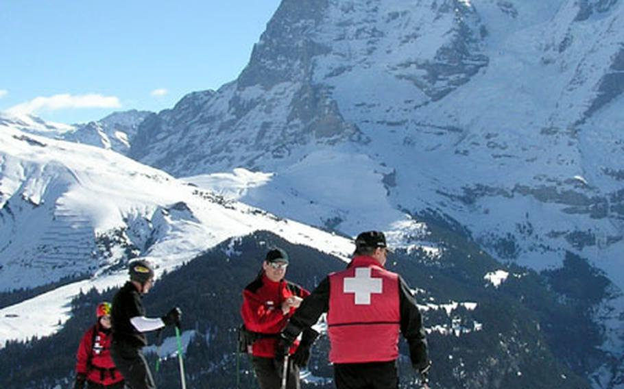 Ski Patrol instructors Tom McCoy and Mike Staszewski, back to camera, take a break in the mountains of Winteregg in Switzerland's Lauterbrunnen Valley during candidate training in March. The Eiger massif and Kleine Scheidegg are in the background.