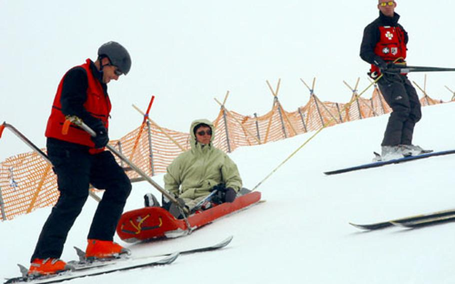 Ski Patrol instructors work on evacuating an injured skier. Here Ben Reed (in the handles) and Brad Pristelski (holding the tail rope) execute a changeover, swapping the tailrope person for the driver of the sled, to allow the driver to rest his legs. They were participating in an instructors' course at Hintertux glacier, Austria.