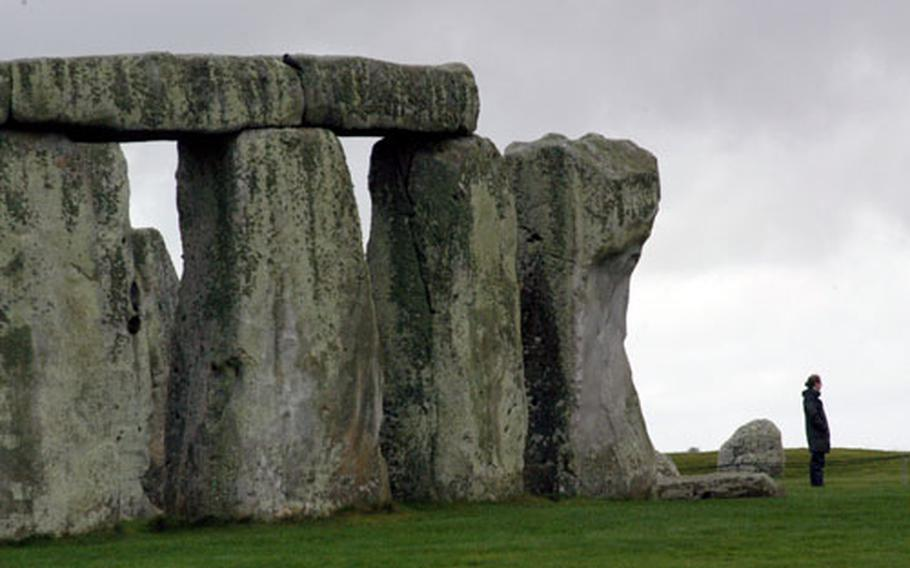 A woman poses for a photo near the ancient site of Stonehenge.