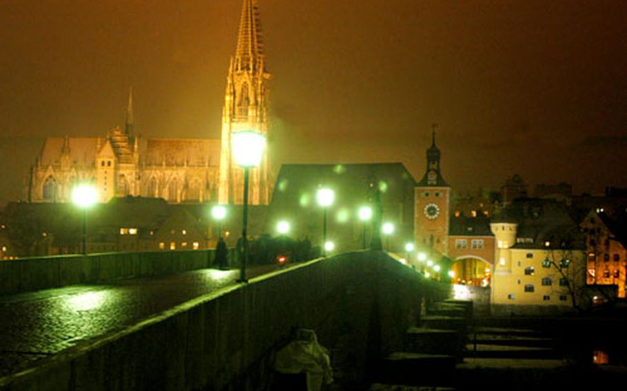 The approach over the Steinerne Brücke (Old Stone Bridge) to medieval Regensburg, Germany, with its towering cathedral offers a marvelous view. Regensburg hosts three Christmas markets.